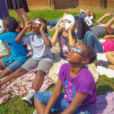 Cowetans look upward as eclipse darkens the sky